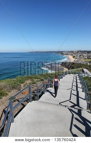 A woman walks along the a newly constructed section of the Newcastle coastal walk on a beautiful sunny day. Bar Beach and Merewether beaches are seen in the distance.