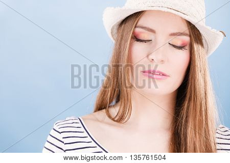 Woman face colorful eye makeup closed eyes straw hat on head smiling having fun closeup. Summer fashion studio shot on blue