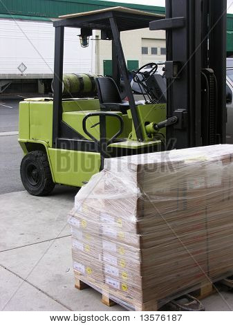 A photo of a forklift unloading a crate with a warehouse in the background