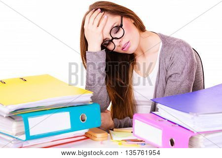Woman working in office suffering from headache. Overworked businesswoman or distressed secretary with pile of documents folders bills on desk. Business and paperwork.