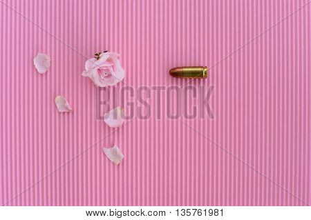 pink rose and metal bullet on pink paper background