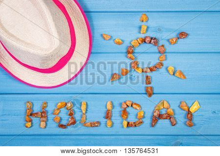 Inscription holiday and shape of sun made of amber stones straw hat on blue boards summer and vacation time