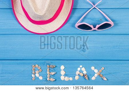 Inscription relax made of seashells straw hat and sunglasses on blue boards summer and vacation time copy space for text