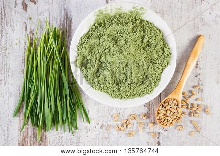Heap Of Young Powder Barley, Barley Grass And Grain On Old Wooden Background