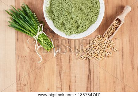 Heap Of Young Powder Barley, Barley Grass And Grain On Wooden Background, Copy Space For Text