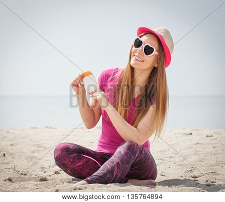 Happy Girl In Straw Hat And Sunglasses With Sun Lotion, Sun Protection On Beach