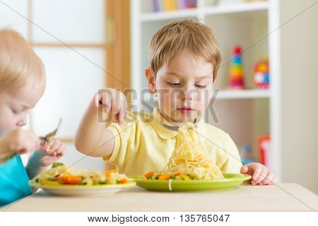 Preschool children eat healthy food in kindergarten or home