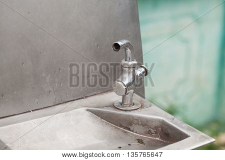 Drinking fountain in park Focus on the faucet and the background blurred