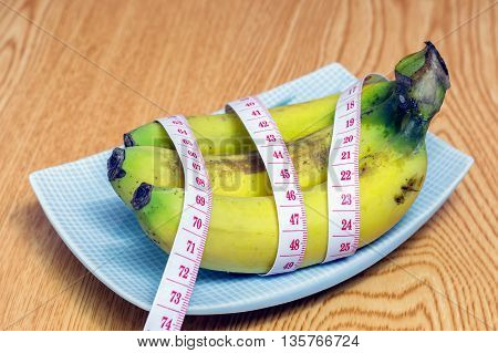 Delicious three banana and measured the meter on wooden background,Healthy food,Diet concept