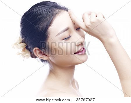 studio portrait of a young asian woman eyes closed side view isolated on white.