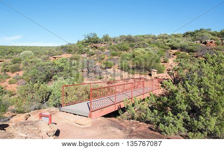 Pedestrian bridge between sandstone cliffs at the Z-bend lookout in Kalbarri National Park with native plants under a clear blue sky in Kalbarri, Western Australia.