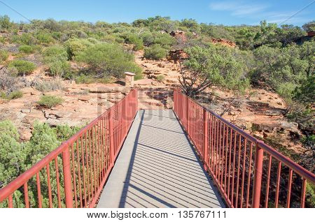 Pedestrian bridge in diminishing perspective at the Z-bend lookout in Kalbarri National Park with red sandstone and native green flora under a clear blue sky in Kalbarri, Western Australia.