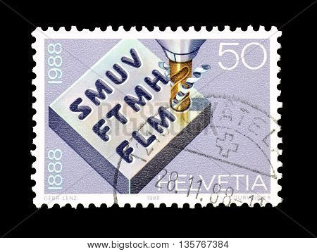 SWITZERLAND - CIRCA 1988 : Cancelled postage stamp printed by Switzerland, that shows Metal block and drill.