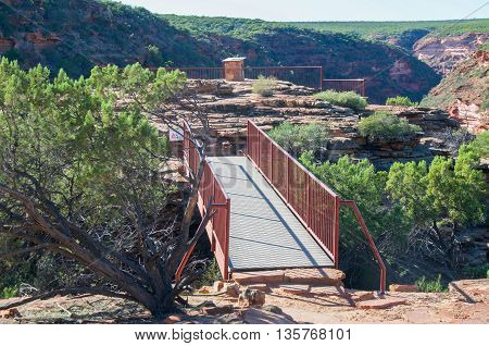 Pedestrian bridge at the Z-bend lookout in Kalbarri National Park with red sandstone and native green flora under a clear blue sky in Kalbarri, Western Australia.