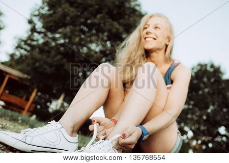 young athletic woman tying shoelaces outdoor