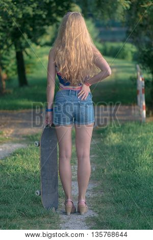 Young skateboarder girl posing outdoor with skateboard