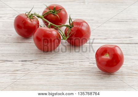 Tomatoes. Branch of tomatoes on white wooden background. Copy space composition. Close up perspectives