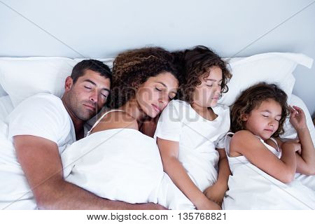 Family sleeping together on bed in bedroom
