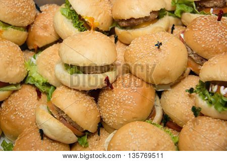 Mini hamburgers with cheese and sesame seeds in buffet corner