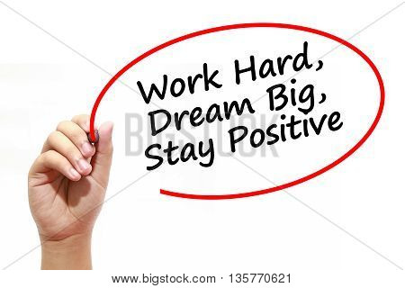 Man writing Work Hard Dream Big Stay Positive with marker on transparent wipe board.
