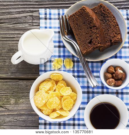 Homemade breakfast option. Homemade chocolate cake, cereals, nuts, hazelnuts, milk for breakfast on a simple gray wooden background with a blue checkered tablecloth.