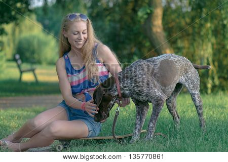 Happy Hipster Girl with her Dog and skateboard in park. Modern Youth Lifestyle Concept.