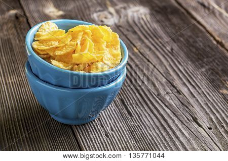 Healthy breakfast. Blue portioned ceramic bowls with corn flakes with on dark wooden background. selective focus