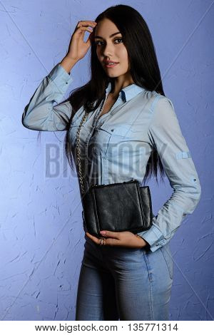 Beautiful Stylish Brunette In Jeans Holding A Black Clutch
