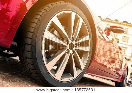 Close up of a tire of a red car in sunset
