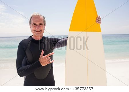 Portrait of senior man with surfboard gesturing hand sign at beach on a sunny day