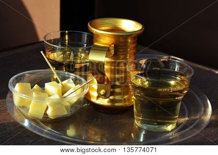 Two glasses of white wine and a plate with pieces of cheese