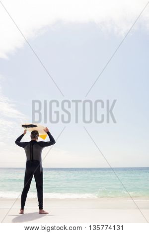 Rear view of senior man holding a surfboard over his head on the beach