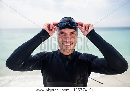 Portrait of young man in wetsuit and swimming goggles standing on beach on a sunny day