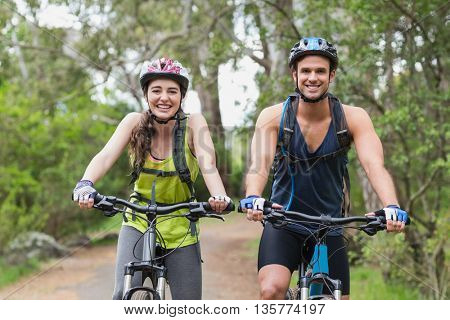 Portrait of young couple with mountain bikes on footpath in forest