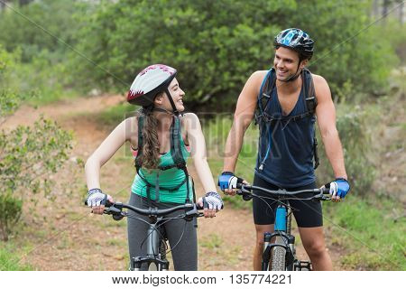 Happy bikers looking at each other on field
