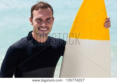 Portrait of happy surfer holding a surfboard on the beach on a sunny day