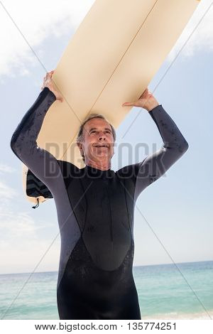 Senior man in wetsuit running on the beach with surfboard over his head
