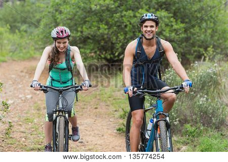 Portrait of couple riding bicycles on dirt road in forest