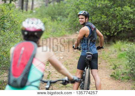 Happy biker looking at woman on dirt road in forest