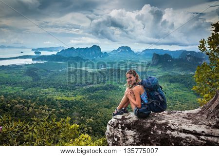 Young backpacker sitting on a cliff and looking to the camera