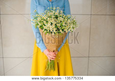 girl holding bouquet of camomiles in paper