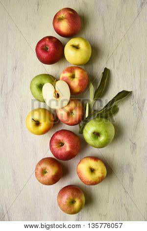 A group of different varieties of apples with leaves on a rustic table. Vertical format viewed from a high angle.