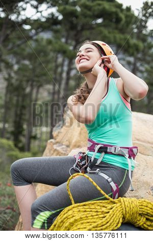 Woman preparing for rock climbing against trees at forest