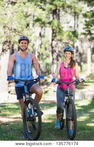 Portrait of smiling young couple with bicycles at forest