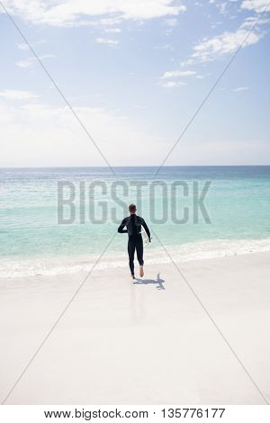 Surfer running towards sea with a surfboard on a sunny day