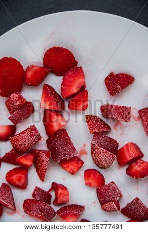 Frozen strawberries sliced into pieces on a white plate