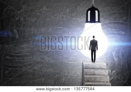 Idea concept with businessman standing on concrete ladder against huge illuminated light bulb on chalkboard background
