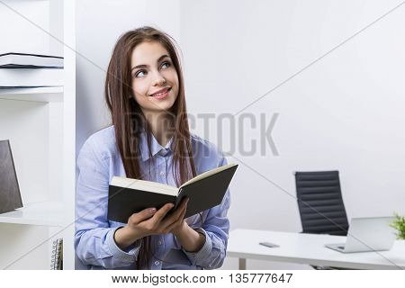 Attractive smiling female going through organizer in modern office with bookshelves and workplace