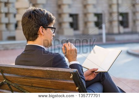 Attractive thoughtful businessman sitting on outdoor bench and writing in blank notepad