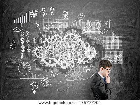 Teamwork concept with thoughtful businessman against chalkboard with gears and business chart sketch